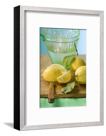 Fresh Lemons with Leaves in Front of Water Jug-Foodcollection-Framed Photographic Print