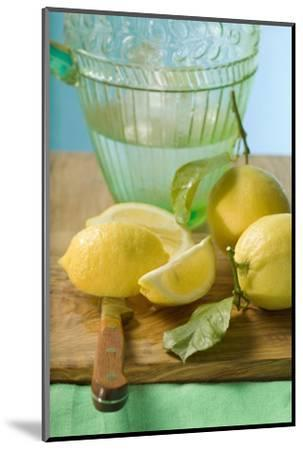 Fresh Lemons with Leaves in Front of Water Jug-Foodcollection-Mounted Photographic Print