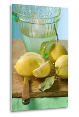 Fresh Lemons with Leaves in Front of Water Jug-Foodcollection-Metal Print