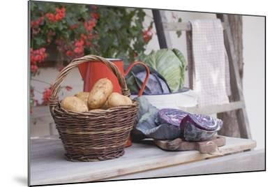 Rustic Still Life with Potatoes and Cabbage in Front of Farmhouse-Eising Studio - Food Photo and Video-Mounted Photographic Print