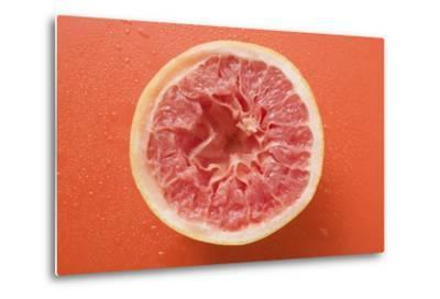 Squeezed Pink Grapefruit on Orange Background-Foodcollection-Metal Print