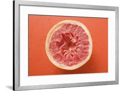 Squeezed Pink Grapefruit on Orange Background-Foodcollection-Framed Photographic Print