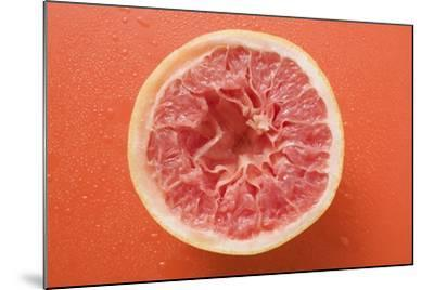 Squeezed Pink Grapefruit on Orange Background-Foodcollection-Mounted Photographic Print