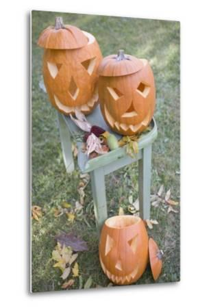 Carved Pumpkin Faces on Garden Table-Foodcollection-Metal Print