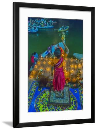 India, Varanasi Young Boy in Pink and Yellow Robes Holds Up an Offering to the Ganges River-Ellen Clark-Framed Photographic Print
