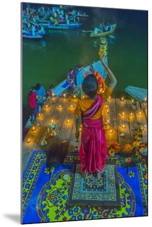 India, Varanasi Young Boy in Pink and Yellow Robes Holds Up an Offering to the Ganges River-Ellen Clark-Mounted Photographic Print