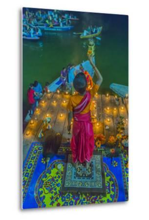 India, Varanasi Young Boy in Pink and Yellow Robes Holds Up an Offering to the Ganges River-Ellen Clark-Metal Print