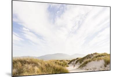 Tramore Beach, Kiltooris, Portnoo, Donegal, Ireland: Woman Walking Through The Dunes Towards Beach-Axel Brunst-Mounted Photographic Print
