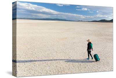 Traveler Rolls A Carry-On Suitcase, The Playa In The Alvord Desert Of SE Oregon-Ben Herndon-Stretched Canvas Print