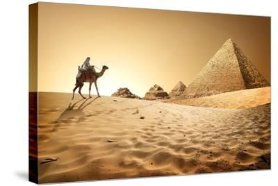 Bedouin on Camel near Pyramids in Desert- Givaga-Stretched Canvas Print