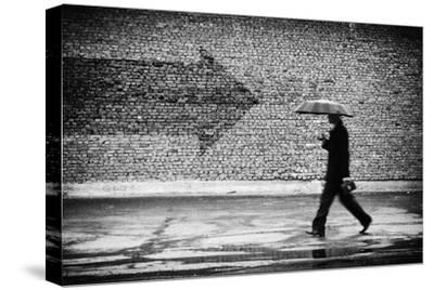 Wrong Way. A Man with Umbrella. Conceptual Image, Film Grain Added-Drop of Light-Stretched Canvas Print