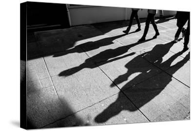 Shadows of Four Walking Pedestrians Projected on the Sidewalk- DrimaFilm-Stretched Canvas Print