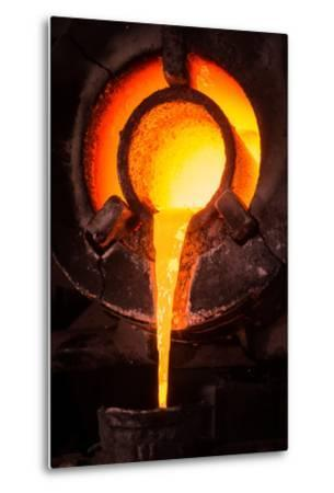 Steel Worker in Protective Clothing Raking Furnace in an Industrial Foundry- FreeProd33-Metal Print