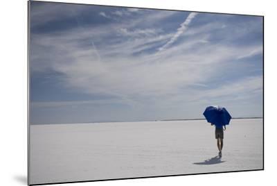 Man Walking With Blue Umbrella On The Bonneville Salt Flats-Lindsay Daniels-Mounted Photographic Print