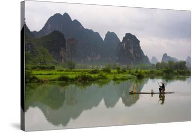 Fisherman on bamboo raft on Mingshi River at sunset, Mingshi, Guangxi Province, China-Keren Su-Stretched Canvas Print