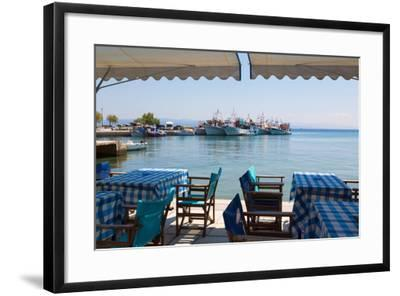 Platanias, Thessaly, Greece. Tables and chairs outside a harbour side restaurant. Fishing boats...--Framed Photographic Print