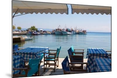 Platanias, Thessaly, Greece. Tables and chairs outside a harbour side restaurant. Fishing boats...--Mounted Photographic Print