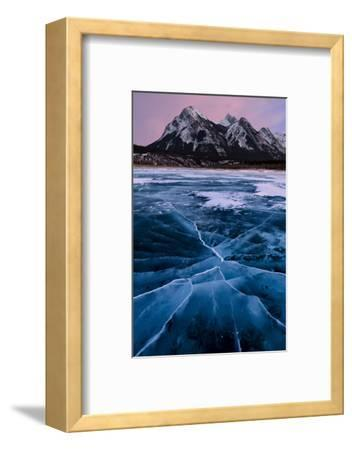 Ice cracks along Abraham Lake in Banff, Canada with purple clouds and scenic mountains-David Chang-Framed Photographic Print