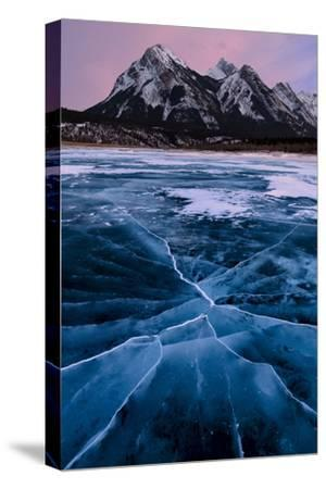 Ice cracks along Abraham Lake in Banff, Canada with purple clouds and scenic mountains-David Chang-Stretched Canvas Print