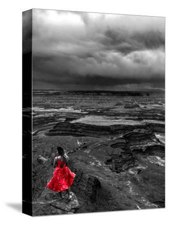 Dark storm clouds over Dead Horse Point State Park with girl in red dress standing near the cliff-David Chang-Stretched Canvas Print