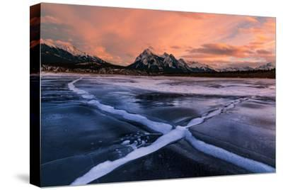 Ice cracks along Abraham Lake in Banff, Canada at sunset with pink clouds and scenic mountains-David Chang-Stretched Canvas Print