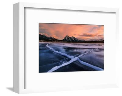 Ice cracks along Abraham Lake in Banff, Canada at sunset with pink clouds and scenic mountains-David Chang-Framed Premium Photographic Print