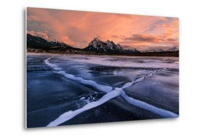 Ice cracks along Abraham Lake in Banff, Canada at sunset with pink clouds and scenic mountains-David Chang-Metal Print