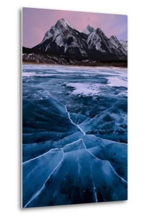 Ice cracks along Abraham Lake in Banff, Canada with purple clouds and scenic mountains-David Chang-Metal Print