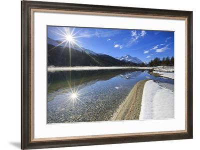 Rays of winter sun illuminate Lake Silvaplana still partially frozen Maloja Engadine Graubunden Can-ClickAlps-Framed Photographic Print