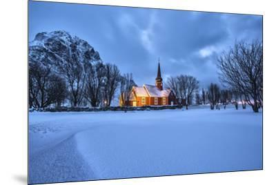 The illuminated church at dusk in the cold snowy landscape at Flakstad Lofoten Norway Europe-ClickAlps-Mounted Photographic Print