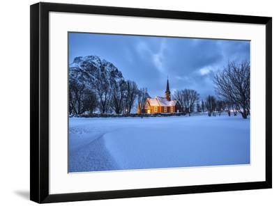The illuminated church at dusk in the cold snowy landscape at Flakstad Lofoten Norway Europe-ClickAlps-Framed Photographic Print