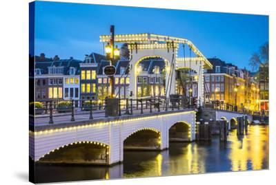 Netherlands, North Holland, Amsterdam. Magere Brug, Skinny Bridge, on the Amstel River at night.-Jason Langley-Stretched Canvas Print