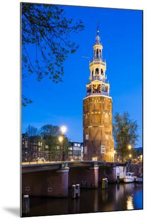 Netherlands, North Holland, Amsterdam. 16th century Montelbaanstoren tower on Oudeschans canal.-Jason Langley-Mounted Photographic Print