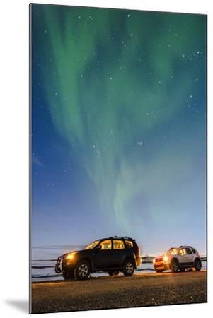 Iceland, Europe. Cars with lights on at night under a starry sky and the northern lights.-Marco Bottigelli-Mounted Photographic Print