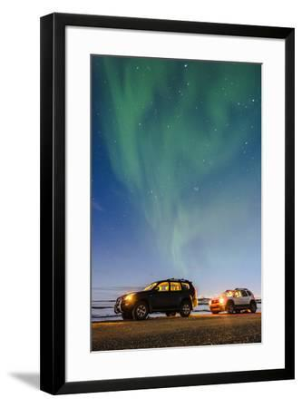 Iceland, Europe. Cars with lights on at night under a starry sky and the northern lights.-Marco Bottigelli-Framed Photographic Print