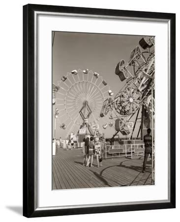 1960s Group of Teens Looking at Amusement Rides on Pier--Framed Photographic Print