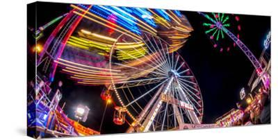 Ferris Wheel and various other funfair rides at night at Nottingham's Goose Fair, Nottingham, Notti-Frank Fell-Stretched Canvas Print