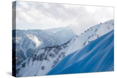 A Snowboarder Cuts a Turn into a Slope in the Backcountry Near Takayama-Max Lowe-Stretched Canvas Print