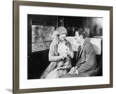 Couple in a Compartment of a Train Looking and Talking with Each Other--Framed Photo