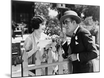 Man and Woman Talking over a Picket Fence--Mounted Photo