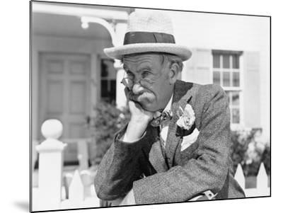 Man Leaning on a Picket Fence Looking into the Distance--Mounted Photo