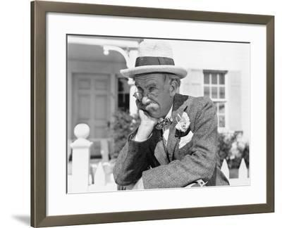 Man Leaning on a Picket Fence Looking into the Distance--Framed Photo