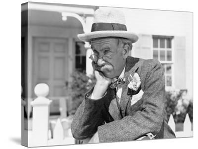 Man Leaning on a Picket Fence Looking into the Distance--Stretched Canvas Print