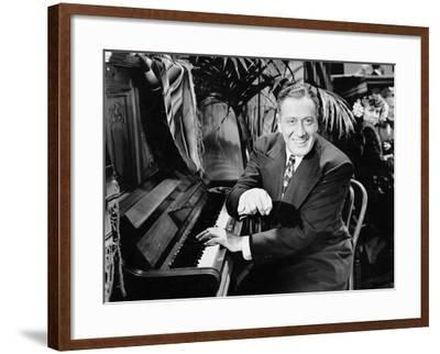Man Sitting Next to a Piano--Framed Photo