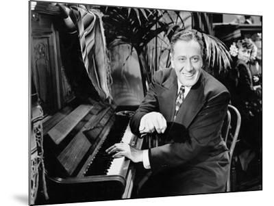 Man Sitting Next to a Piano--Mounted Photo