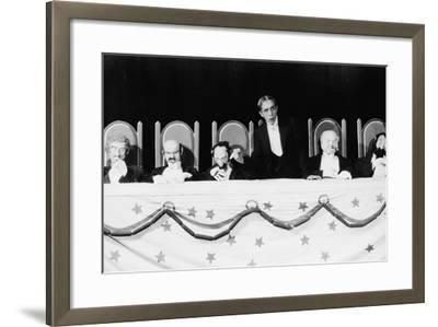 Man with Row of Seated Puppets--Framed Photo