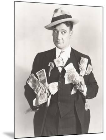 Man Holding Wads of Fake Money--Mounted Photo