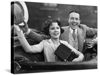 Portrait of Happy Couple Waving in Car--Stretched Canvas Print