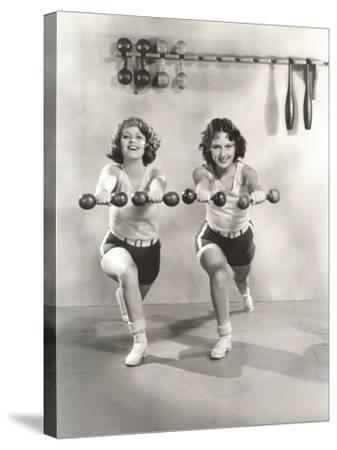 Two Women Exercising with Dumbbells at Gym--Stretched Canvas Print
