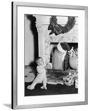 Santa Claus with a Little Boy in Front of a Fireplace--Framed Photo